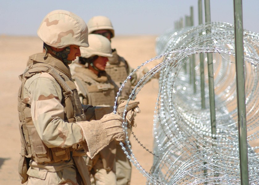 US Navy 090903-N-4440L-246 Seabees assigned to Naval Mobile Construction Battalion (NMCB) 74, install concertina wire during a three-mile expansion of Camp Leatherneck