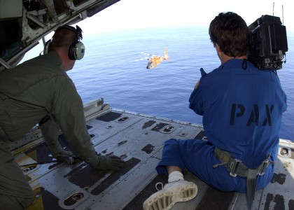 US Navy 021220-N-7590D-025 U.S. Coast Guard air crewman looks on as Bill Paris, a commercial cameraman captures footage of an HH-65A Helicopter