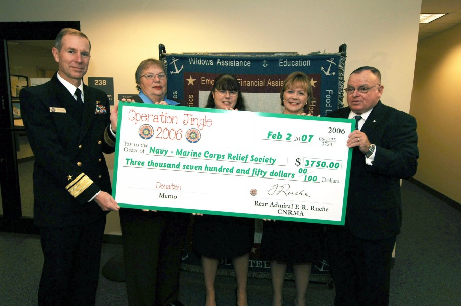 US Navy 070202-N-5758H-002 Commander, Navy Region Mid-Atlantic (CNRMA) Rear Adm. Rick Ruehe, presents a $3,750 check from the proceeds of Operation Jingle