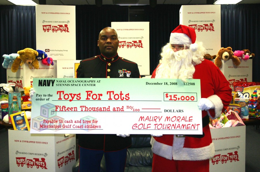 US Navy 081218-N-6981B-006 Gunnery Sgt. Theodis Jones accepts a $15,000 check for the U.S. Marine Corps annual Toys for Tots campaign