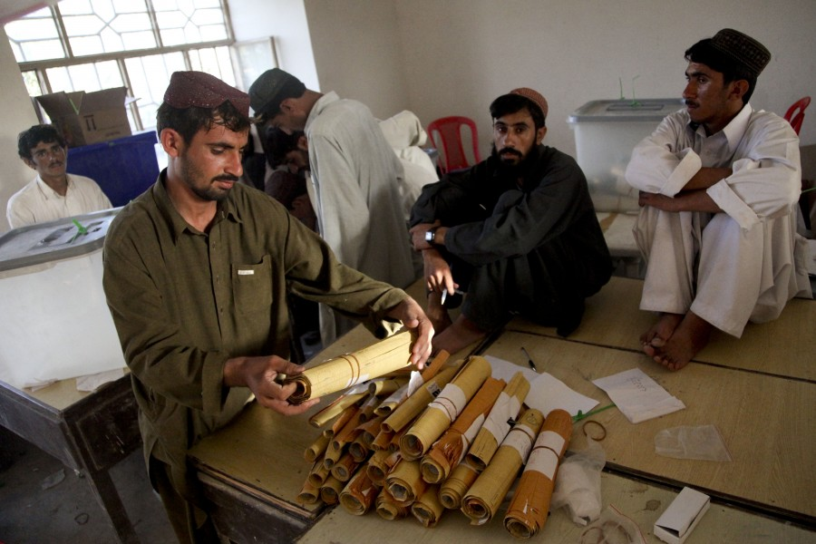 US Navy 090821-M-0440G-031 Afghan presidential election workers count and organize election ballots at a local school in the Nawa District