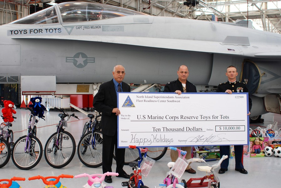 US Navy 091218-N-1878M-001 U.S. Marine Corps Reserves annual Toys for Tots campaign hold a ceremonial check representing a $10,000 donation by the employees of FRCSW during festivities