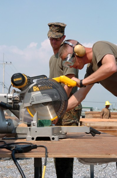 US Navy 050111-M-3295H-006 Lance Cpl. Kevin Shepard, foreground, and Pfc. Anthony Nichols, both assigned to the 3rd Marine Expeditionary Force (MEF), use a radial saw to cut plywood