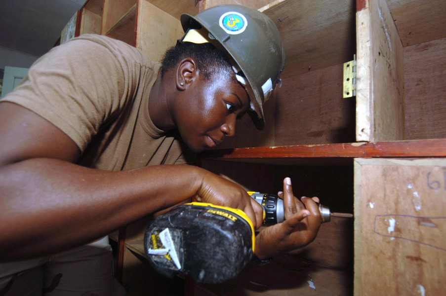 US Navy 051226-N-4374S-012 Store Keeper 2nd Class Sparkole Dyeth, a U.S. Navy Seabee assigned to Naval Mobile Construction Battalion Three (NMCB-3), helps refurbish a wooden cabinet