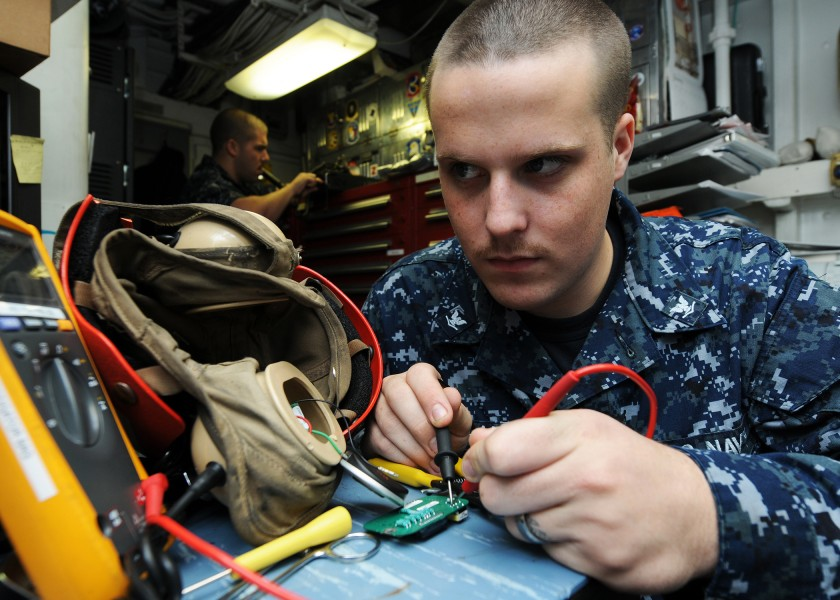 US Navy 120125-N-KQ416-008 Electronics Technician 3rd Class Michael Schranck takes a resistance reading on a circuit card for a flight deck cranial
