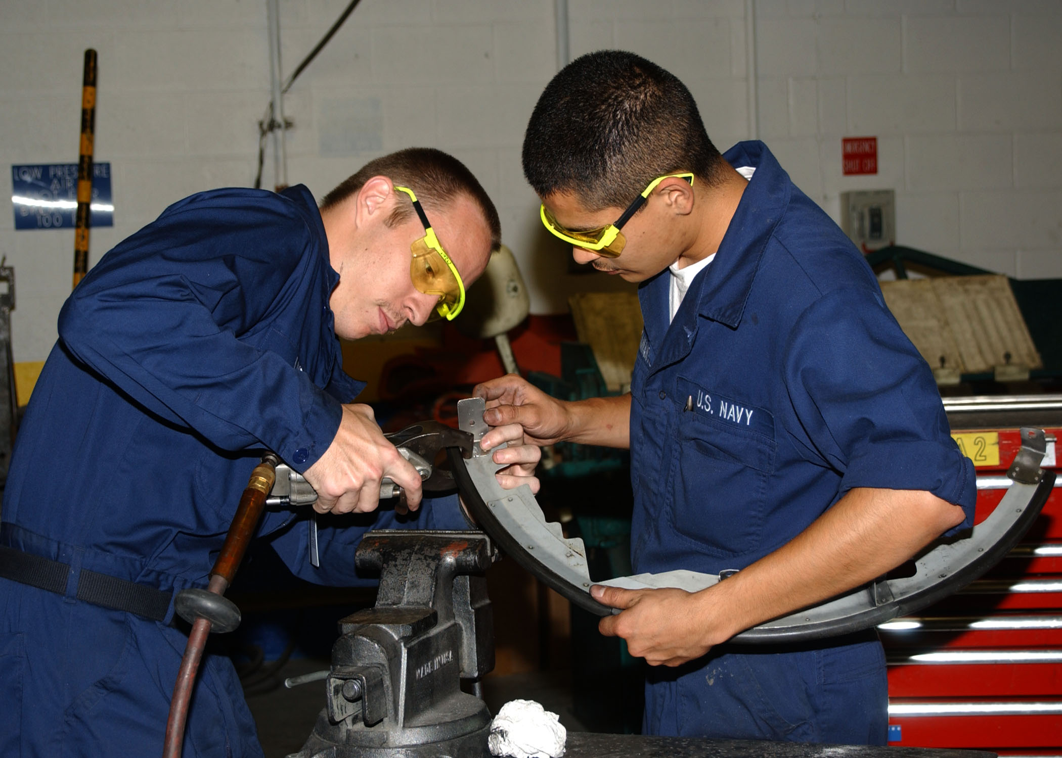 US Navy 030618-N-3970R-001 Aviation Structural Mechanic 2nd Class Jason Lively and Aviation Mechanic Airman Rafael Bustamente work together to rivet an air baffle