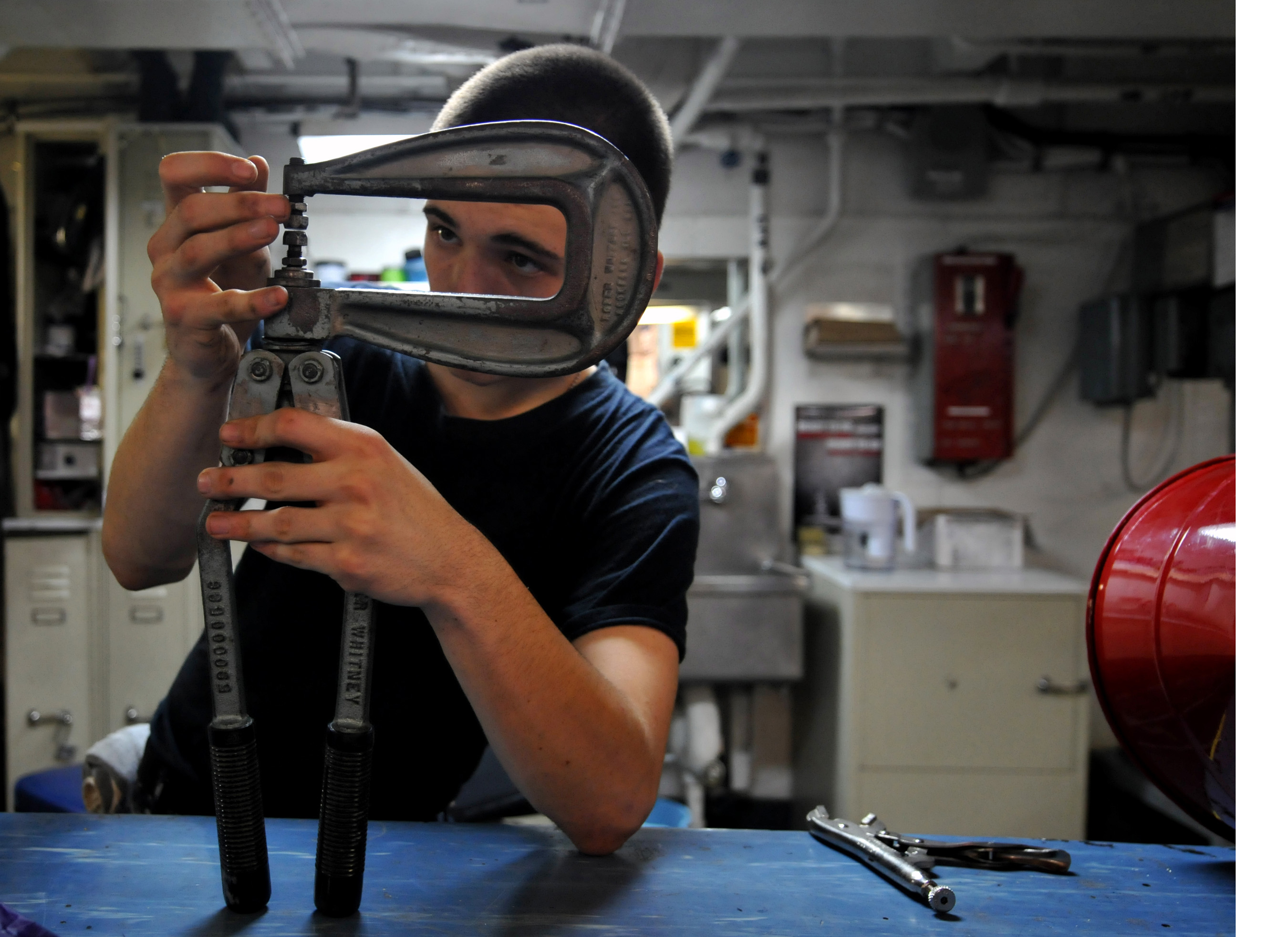 US Navy 120110-N-ZZ999-401 Airman Kaleb White adjusts a rivet squeezer while repairing a foreign object damage bucket