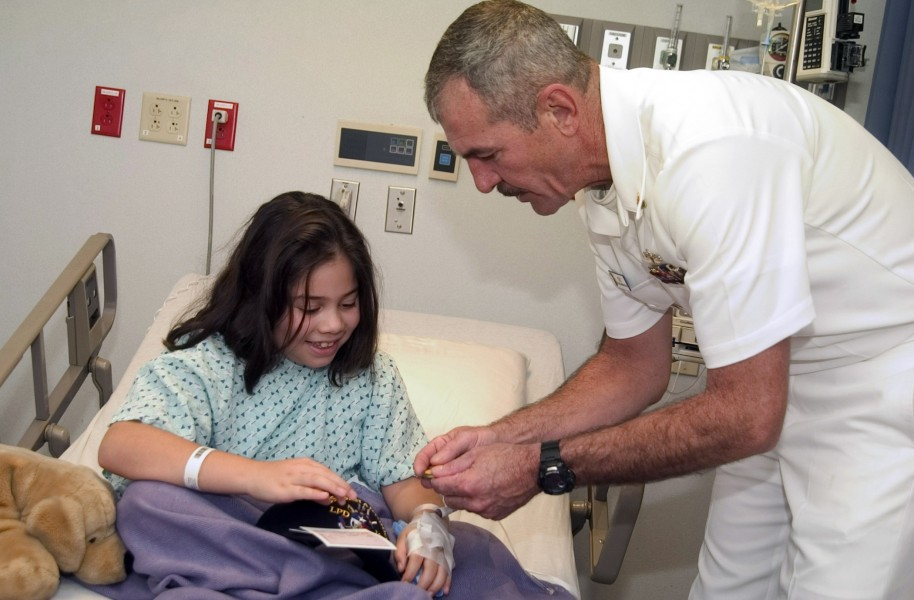 US Navy 061108-N-3750S-140 Chief Master-at-Arms Ed Stift shares coins and talks with a young girl at Methodist Children's Hospital
