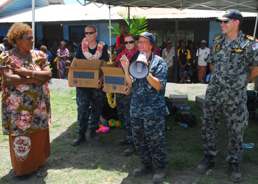 US Navy 100907-N-4044H-320 Capt. Lisa M. Franchetti presents a command coin to Jacobeth Bakut, head teacher of Malaguna Primary School