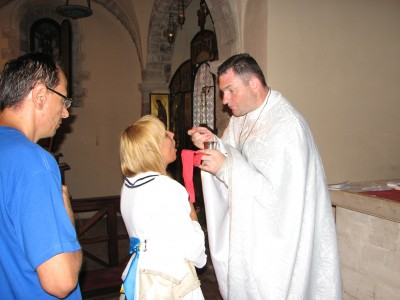 A young woman taking the Holy Communion from a Greek-Catholic priest, Italy, summer 2011