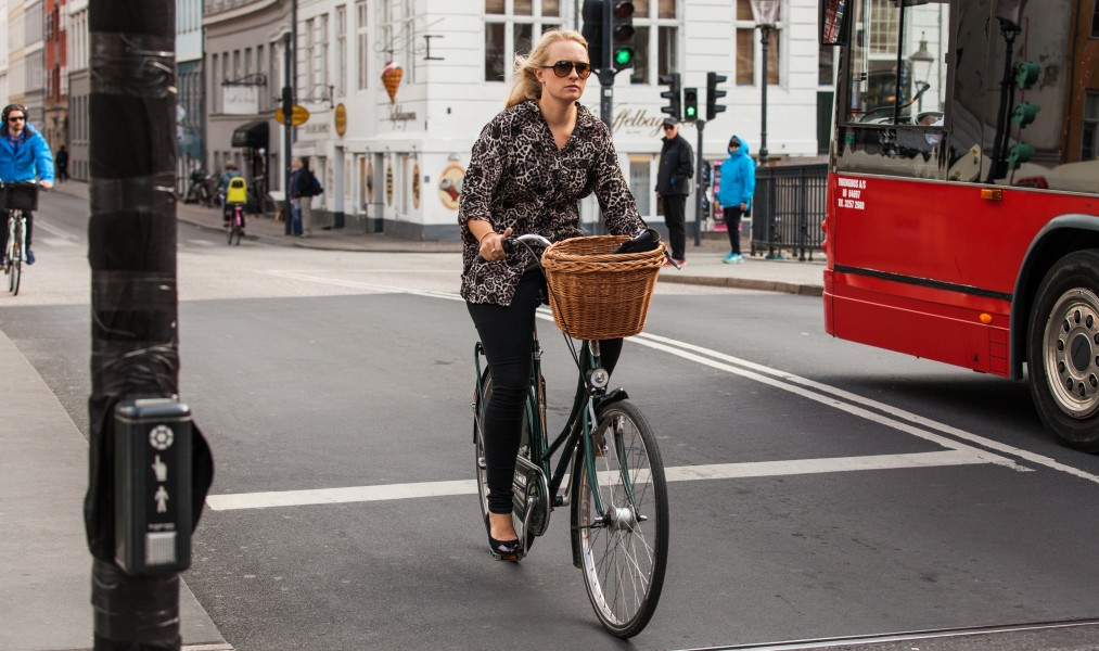 a blond young woman on a bike in Copenhagen, Denmark, June 2014, picture 59