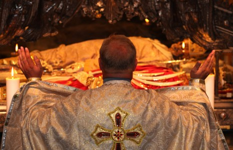 a priest praying near relics in Saint Ambrose basilica, Milan, August 2013, picture 9