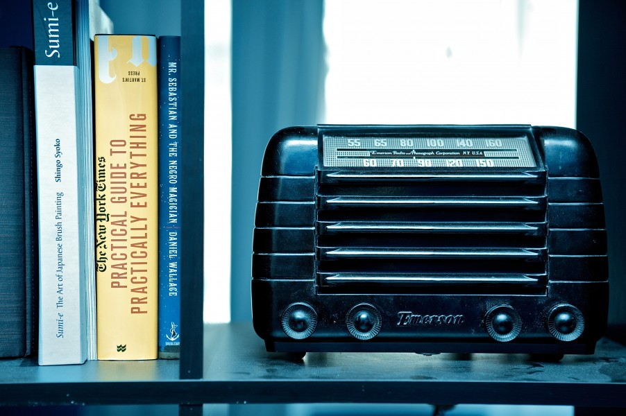 Old Dusty Radio on a shelve with books on the left