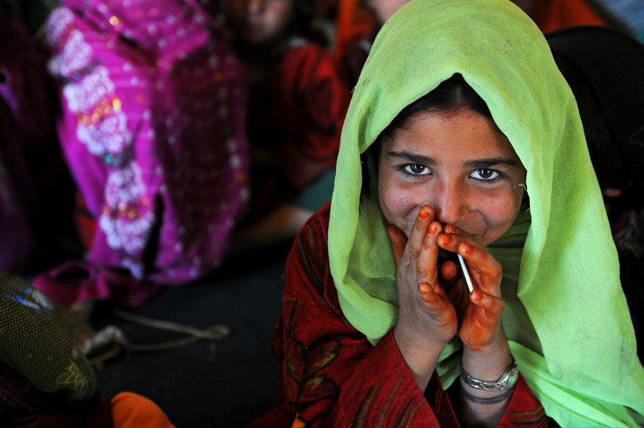 A young Afghan girl smiles shyly