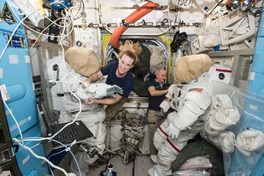 ISS-48 Kate Rubins and Jeff Williams outfit spacesuits inside the Quest airlock