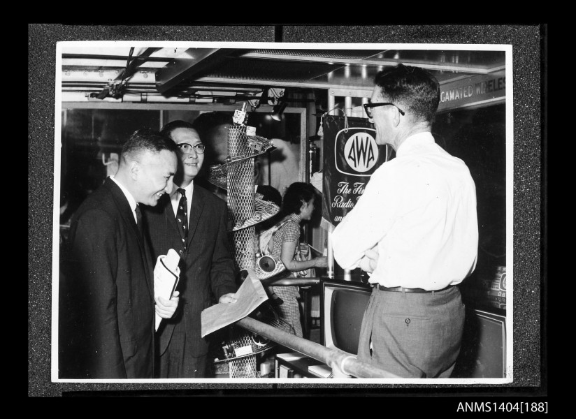Two men looking at an AWA company display on board a trade ship (21665080355)