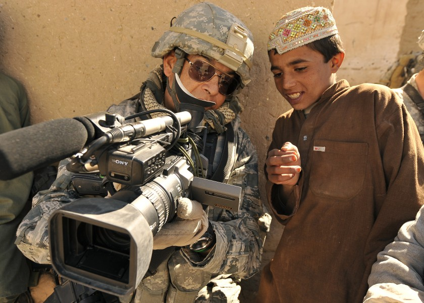 U.S. Air Force Master Sgt. Robert Carreon, with the 4th Combat Camera Squadron, shows his video recording to a student at the Wazi Muhammad Khan School in Hutal, Afghanistan, Jan. 7, 2010 100107-F-PU334-121