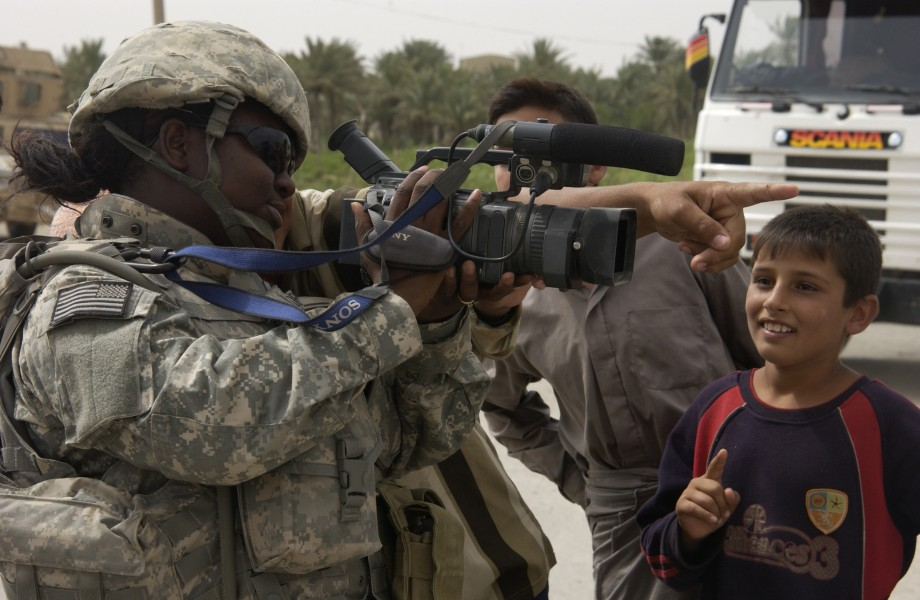 U.S. Air Force SrA Chalanda Roberts of, Joint Combat Camera, shows iraqi children what she see's through the viewfinder of her video camera at a traffic control point located near Abusayda, Iraq on June 1 070601-F-AD344-077