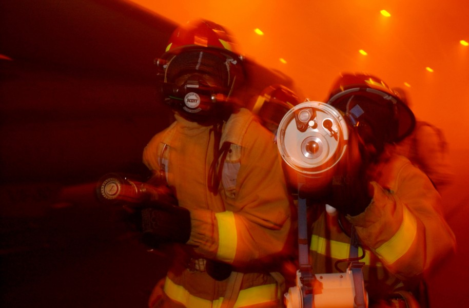 US Navy 040419-N-9851B-076 A fire team uses a Naval Firefighter Thermal Imager (NFTI) while advancing on a simulated fire
