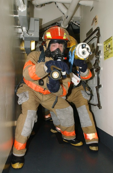 US Navy 040802-N-1513W-208 Damage Controlmen participating in a fire drill, use a Naval Firefighter Thermal Imaging (NFTI) device to simulate seeing through smoke in a workspace, during a drill aboard the aircraft carrier USS J
