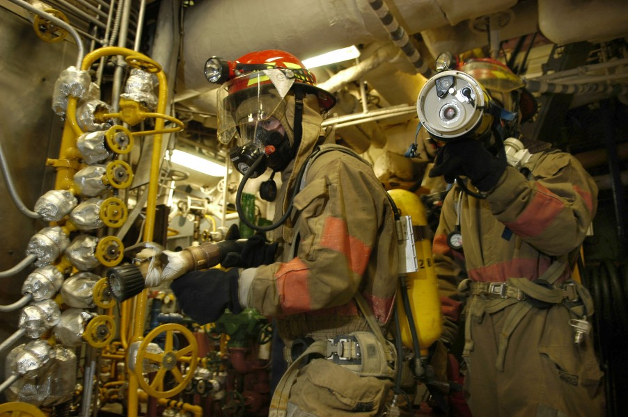 US Navy 050826-N-3136P-108 An on-scene leader uses a Naval Firefighter Thermal Imaging Device (NFTI) to search for fires during a main space fire drill aboard the conventionally-powered aircraft carrier USS Kitty Hawk (CV 63)
