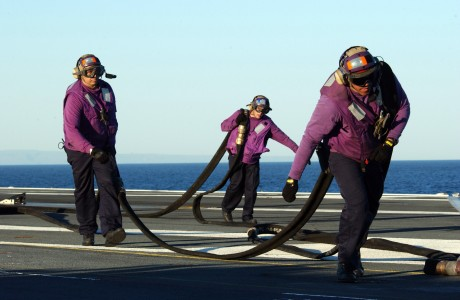 US Navy 050203-N-8148A-090 Aviation Boatswain's Mates return a fuel hose to its proper position after refueling an MH-60S Knighthawk helicopter