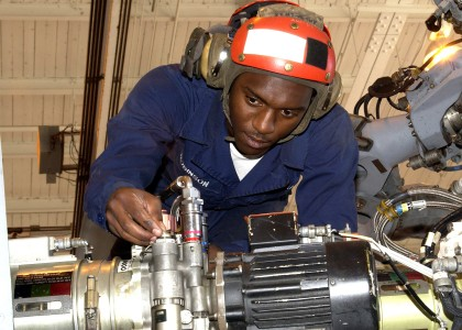 US Navy 060405-N-1126D-004 Airman Kennie Robinson performs routine maintenance on an SH-60 Seahawk helicopter hydraulic pump