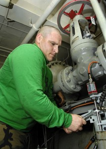 US Navy 081022-N-4954I-006 Aviation Boatswain's Mate (Equipment) 3rd Class Andy Boucher performs maintenance on an aircraft catapult hydraulic system