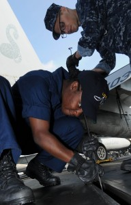 US Navy 091203-N-3038W-048 Aviation Boatswain's Mate (Equipment) Airman Latia Davis and Aviation Boatswain's Mate (Equipment) Airman Kevin Rooker perform maintenance on a catapult