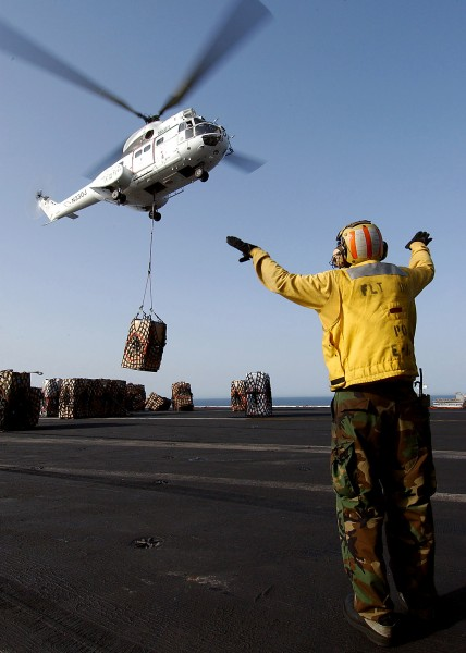 US Navy 040527-N-7871M-047 Aviation Boatswain's Mate 2nd Class Francis Gardner, of Waukegan, Ill., directs an Aerospatiale SA330 Puma helicopter after picking up a pallet of supplies