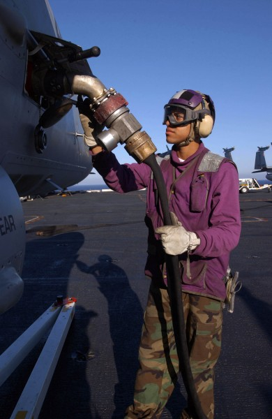 US Navy 041114-N-2143T-016 Aviation Boatswain's Mate Airman Edward Abrams of Seattle, Wash., fuels an F-A-18 Hornet aboard the aircraft carrier USS Nimitz (CVN 68)