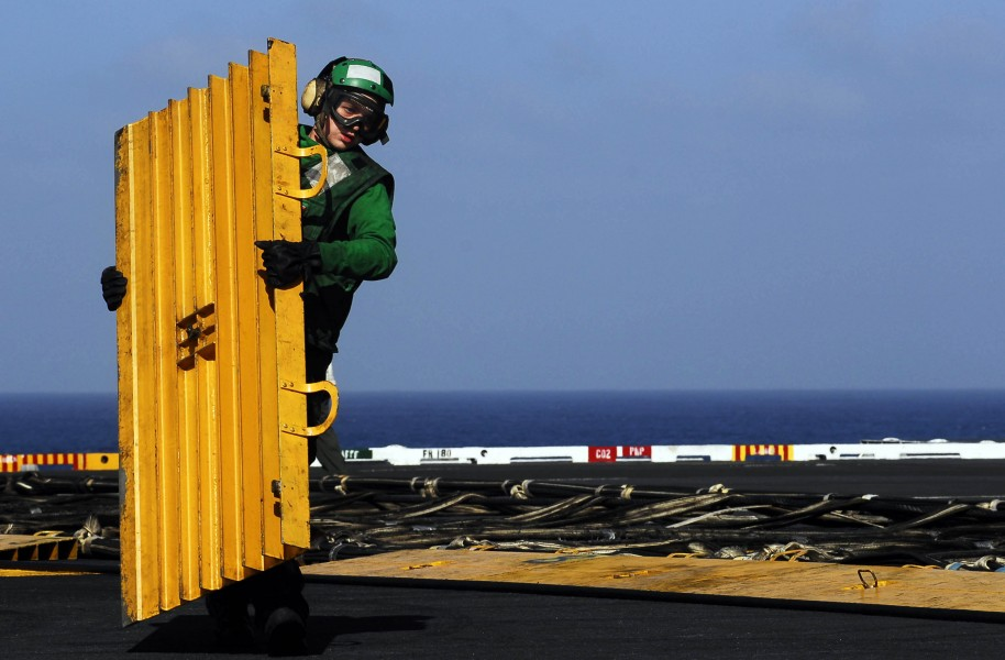US Navy 081010-N-9928E-042 Aviation Boatswain's Mate (Equipment) Airman Zach Hill removes a barricade deck ramp