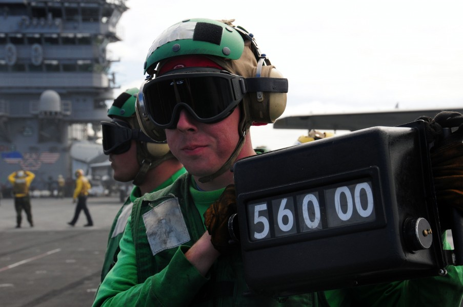 US Navy 090225-N-3946H-050 Aviation Boatswain's Mate (Equipment) 3rd Class Doug Bellew displays the weight of an F-A-18F Super Hornet
