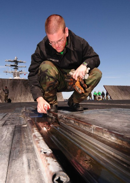 US Navy 090324-N-9760Z-012 Aviation Boatswain's Mate (Equipment) Airman Nicoles Schulmeister, lubricates the nose gear launch assembly of catapult number three