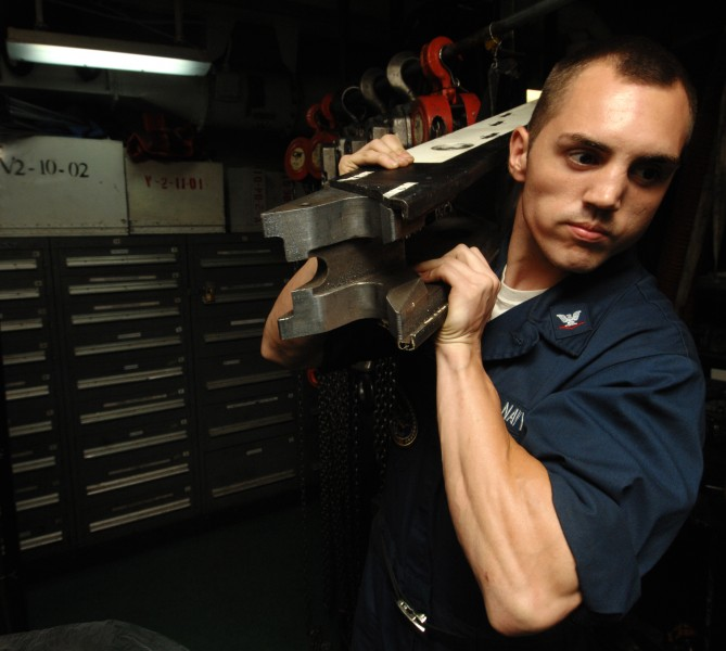 US Navy 100721-N-6582H-024 Aviation Boatswain's Mate (Equipment) 3rd Class Victor Guarnieri grabs a spreader from the maintenance tool room aboard USS Harry S. Truman (CVN 75)