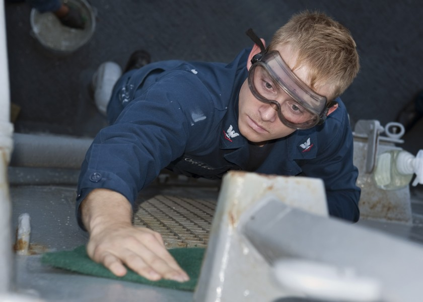 US Navy 110923-N-FI736-047 Hospital Corpsman 3rd Class Logan Ortlieb cleans the bulkhead on the weather decks of the guided-missile destroyer USS A