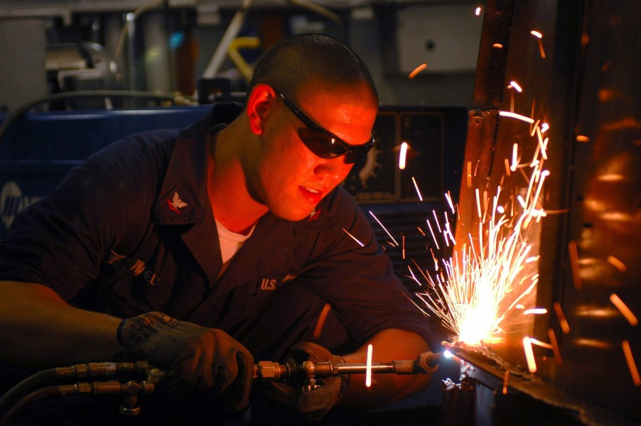 US Navy 061027-N-8119R-159 Hull Maintenance Technician 3rd Class Jeremy Hanel uses a cutting torch to cut apart old shelving aboard the nuclear-powered aircraft carrier USS Nimitz (CVN 68)