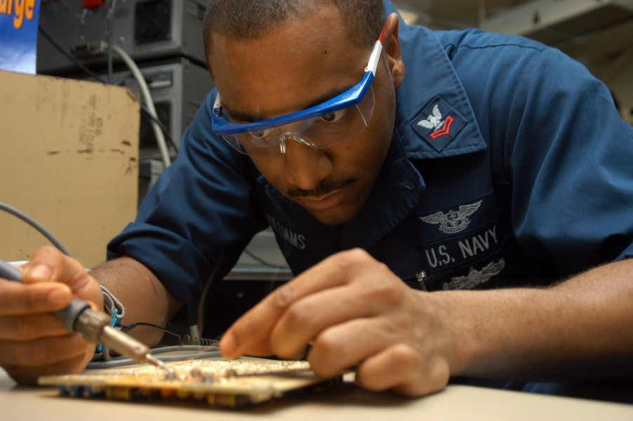US Navy 040831-N-7568S-002 Aviation Electronics Technician 2nd Class Kevin Williams, of Decatur, Ga., repairs a circuit card for a UPM-136 transponder