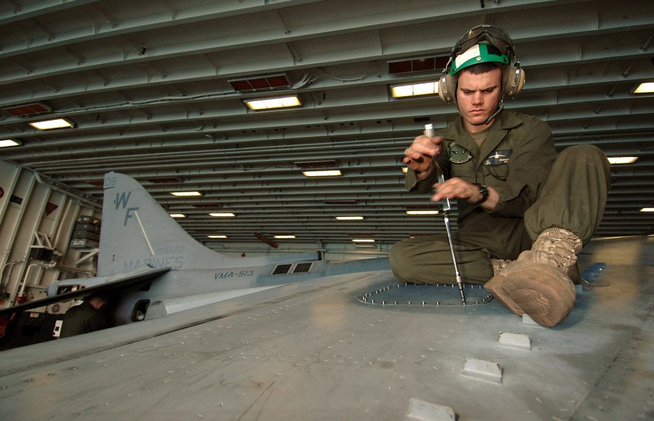 US Navy 070314-N-3211R-019 Lance Cpl. Nathan Redfearn, a native of Herrin, Ill., uses a speeder to remove an access panel on the wing of an AV-8B Harrier, in order to conduct a phase inspection
