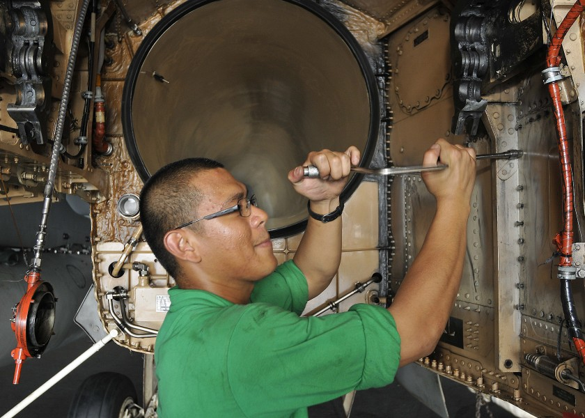 US Navy 100929-N-7103C-002 Aviation Structural Mechanic (Equipment) Airman Frederick Copuyoc removes bolts from the access panel of an F-A-18C Horn
