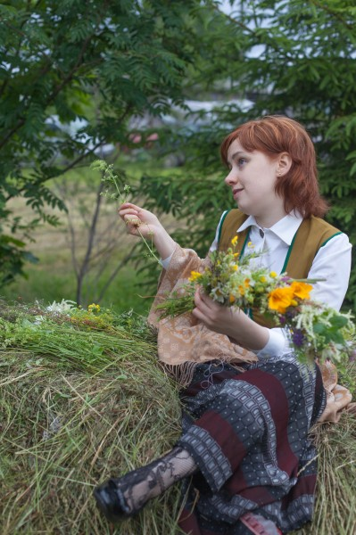 Ieva creating a crown from flowers, Midsummer festival, Latvia