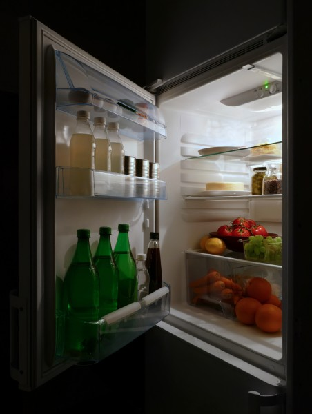 Open refrigerator with food at night