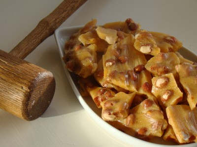 Golden peanut brittle with wooden hammer