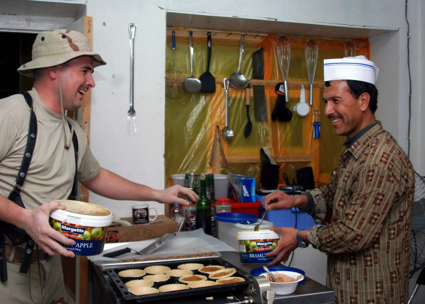 US Navy 071030-N-7415V-003 Culinary Specialist 2nd Timothy Wright, assigned to the Combined Security Transition Command-Afghanistan, teaches Nasim, the Afghan cook, how to make an apple dessert