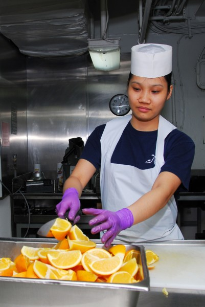 US Navy 100111-N-3327M-141 Culinary Specialist 3rd Class Ruibing Cai cuts oranges in the mess decks aboard the aircraft carrier USS Nimitz (CVN 68)