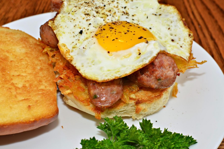 Mmm... fried egg, sliced sausage, and hash browns on a grilled bun (6226666569)