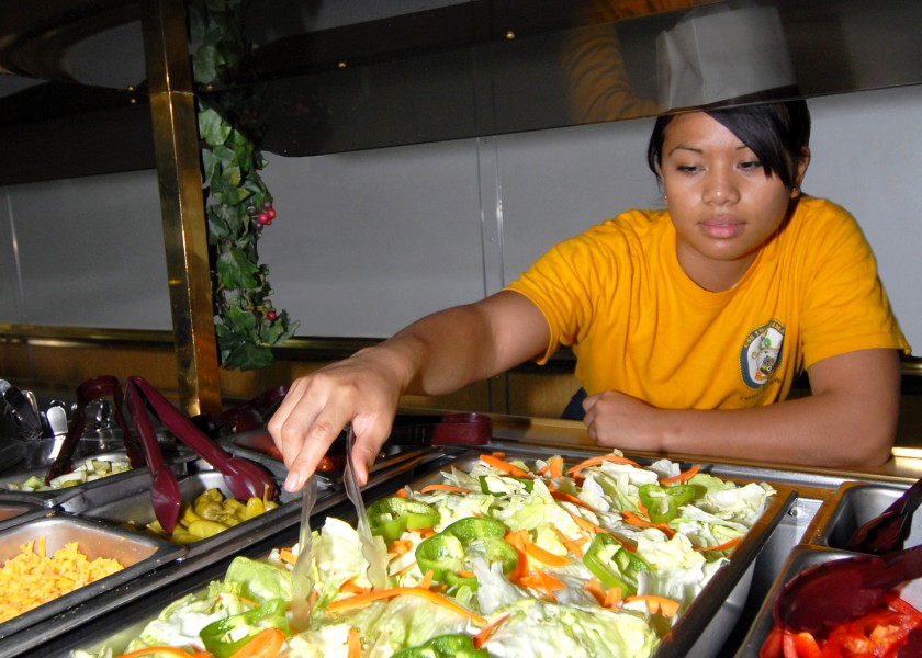 US Navy 060906-N-4856C-005 Gunner's Mate Seaman Juntine R. Velayo from Las Vegas, Nev., prepares the salad bar in the Wardroom Mess aboard the amphibious assault USS Iwo Jima (LHD 7)
