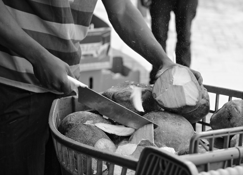 A man makes his living opening and selling coconuts on the street (Fordsburg, 2015)