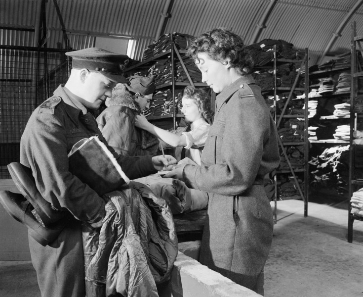 A WAAF section officer and her assistant issue new items of flying kit to aircrew at an RAF bomber station, August 1944. CH13713