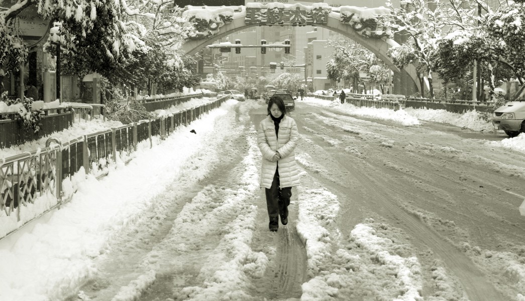 A woman is walking in the snow